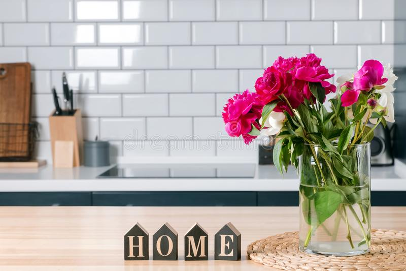 De mooie roze pioenen in een glasvaas die zich op bevinden kithcen met de witte muur van de baksteentegel stock foto's