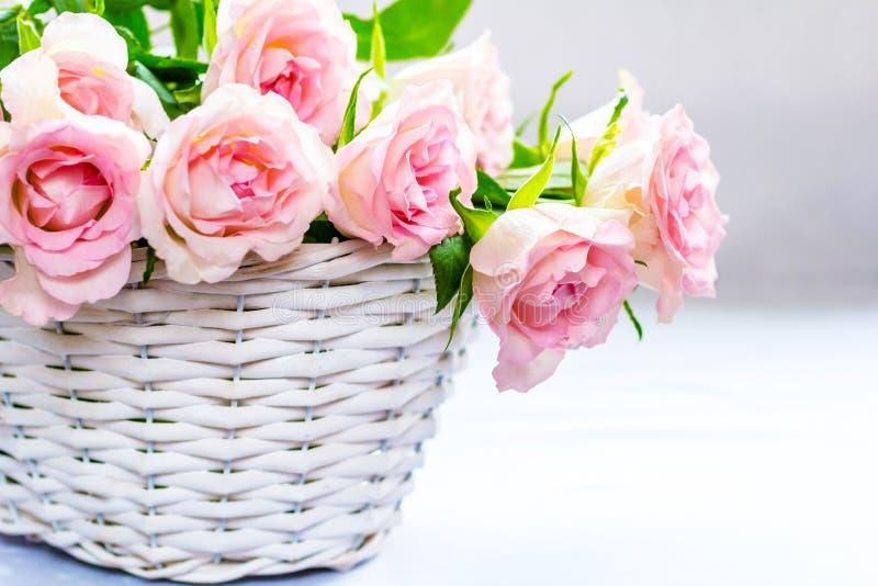 De mooie, roze rozen in een witte mand sluiten omhoog royalty-vrije stock foto