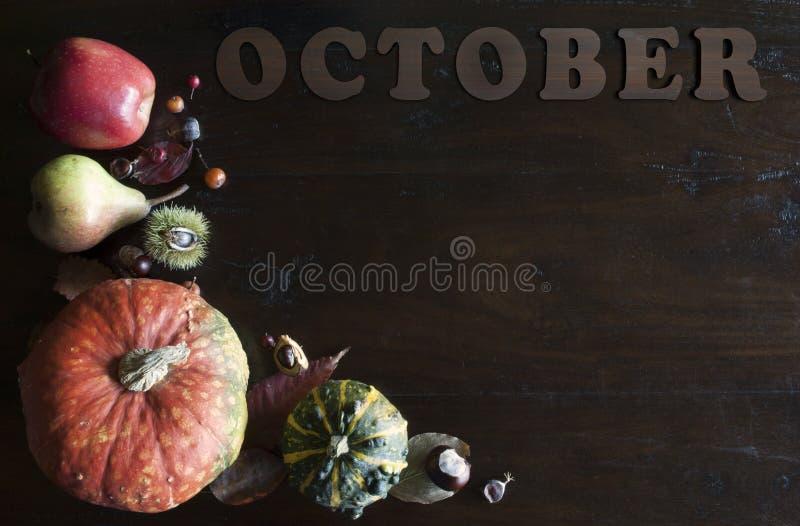 De mooie rustieke dalingsvlakte legt met bladeren, pompoenen, kastanjes en brieven oktober op houten achtergrond stock afbeelding