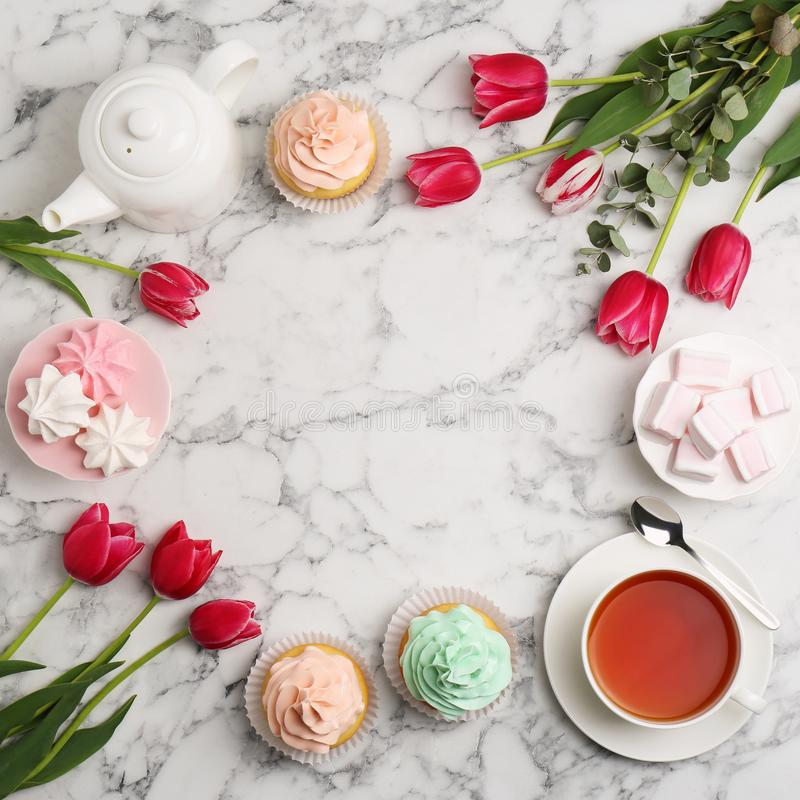 De mooie samenstelling met thee, desserts en tulpen op marmeren vlakke achtergrond, legt royalty-vrije stock fotografie