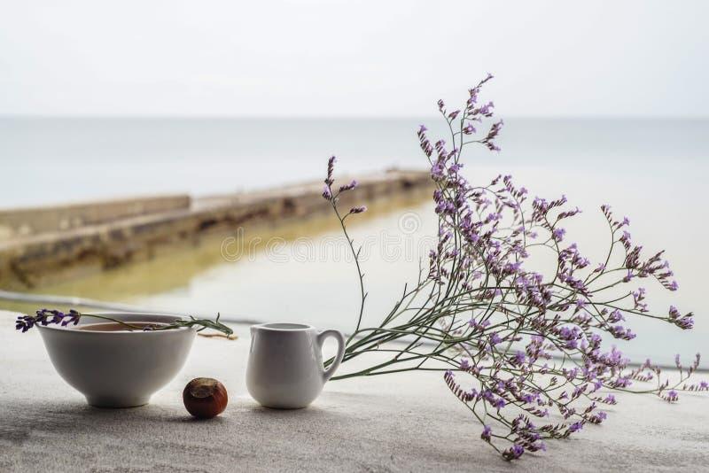 De mooie samenstelling van berglavendel bloeit en heerlijke lunch, hete soep in een witte plaat, een klein schip met zure room stock fotografie