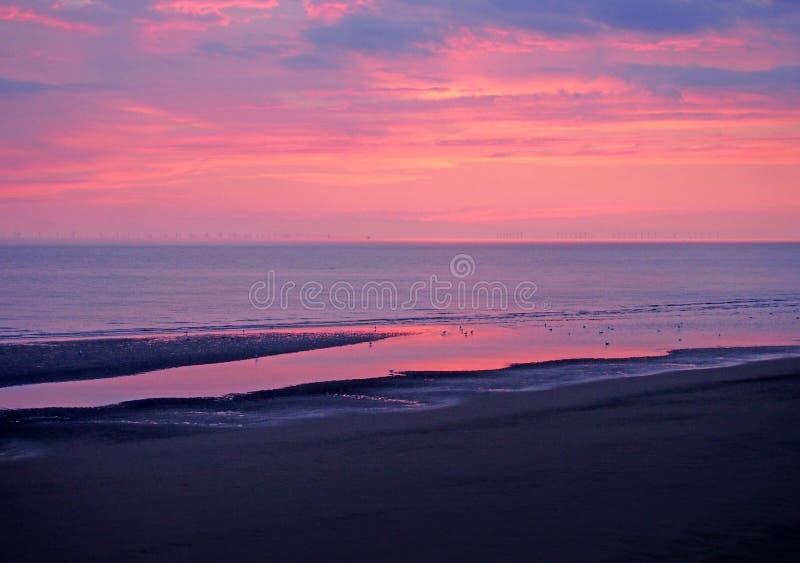 De mooie schemering dramatische purpere hemel over het overzees met kleurrijke avondwolken dacht in kalm water en donker strand n stock foto's