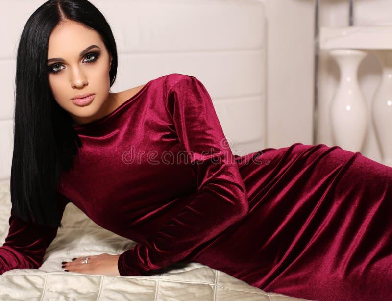 De mooie sensuele vrouw met donker haar draagt elegante kleding, die in slaapkamer stellen royalty-vrije stock foto
