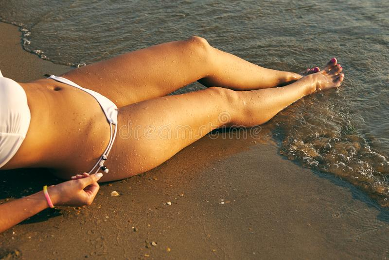 De mooie sexy benen van vrouwen met waterdruppeltjes op het strand stock afbeeldingen