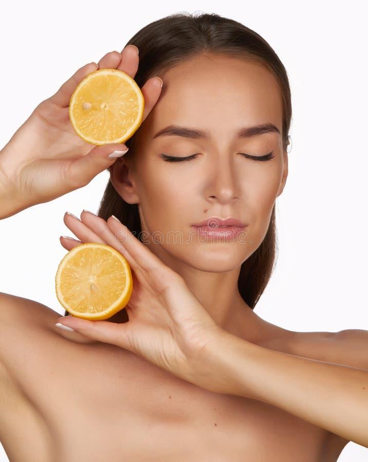 De mooie sexy donkerbruine vrouw met citrusvrucht op een witte achtergrond, gezond voedsel, smakelijk voedsel, organisch dieet, g royalty-vrije stock foto's