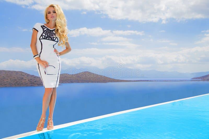 De mooie sexy jonge vrouw van blonde krullend lang haar bevindt zich in het korte wit die sexy dure kleding uitdagen bij het zout stock foto