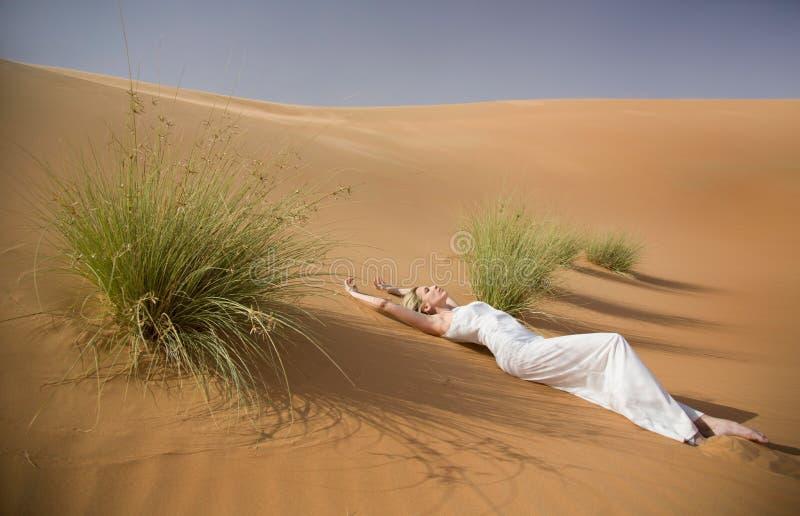 De mooie sexy vrouw legt in whtekleding tussen tuffets in zandwoestijn royalty-vrije stock afbeelding