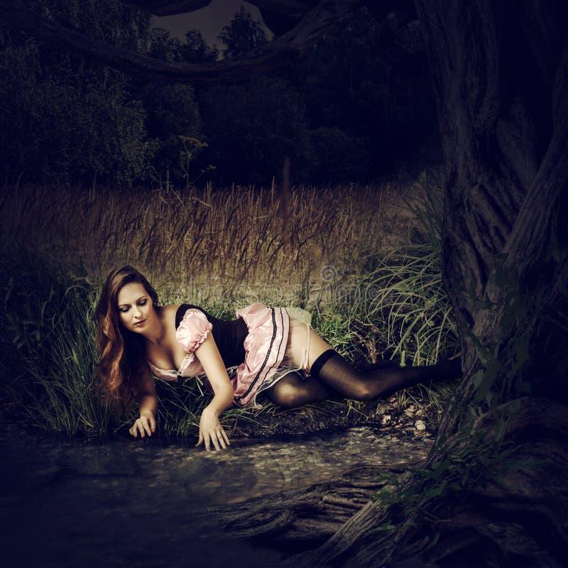 De mooie sexy vrouw ligt in donker bos royalty-vrije stock afbeelding