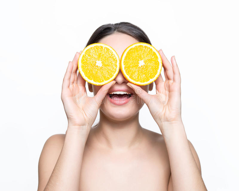 De mooie sinaasappelen van de meisjesholding voor ogen stock foto's