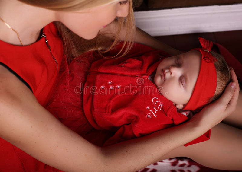 De mooie slaap van het babymeisje in de handen van het tedere mamma stock fotografie