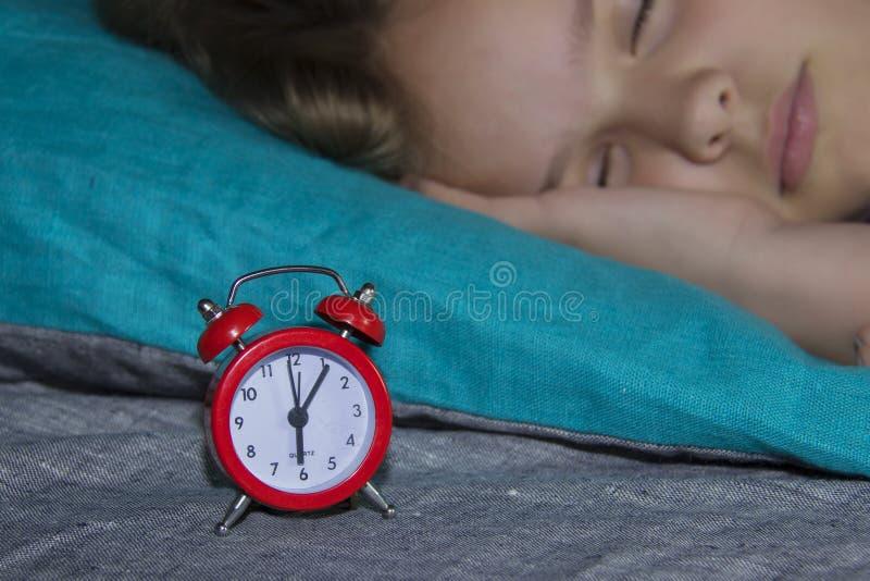 De mooie slaap van het kindmeisje op de achtergrond van een rode wekker die haar in de ochtend zal wekken stock foto