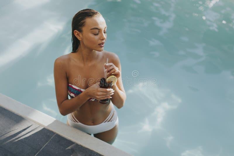 De mooie slanke vrouw in bikini het ontspannen en drinkt cocktail op poolside van een zwembad stock foto