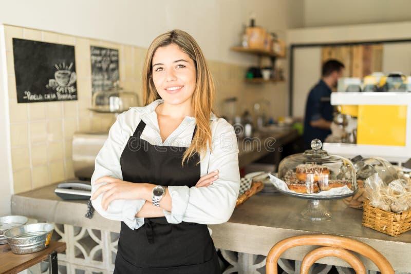 De mooie Spaanse eigenaar van de koffiewinkel stock foto