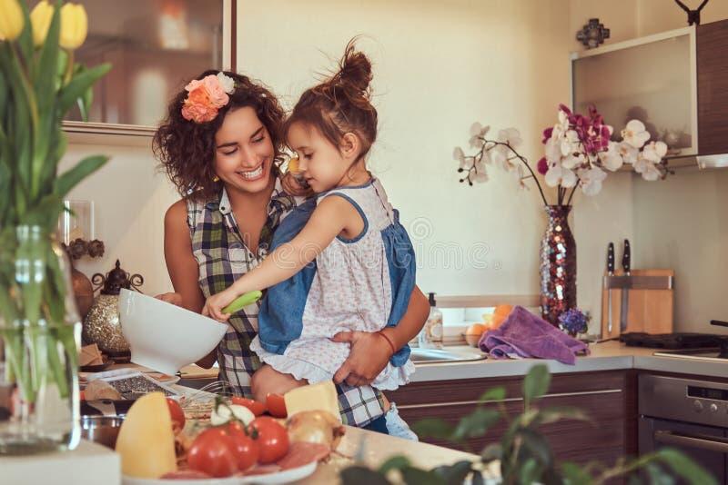 De mooie Spaanse moeder onderwijst haar leuke kleine dochter pizza in de keuken voorbereidt royalty-vrije stock afbeelding