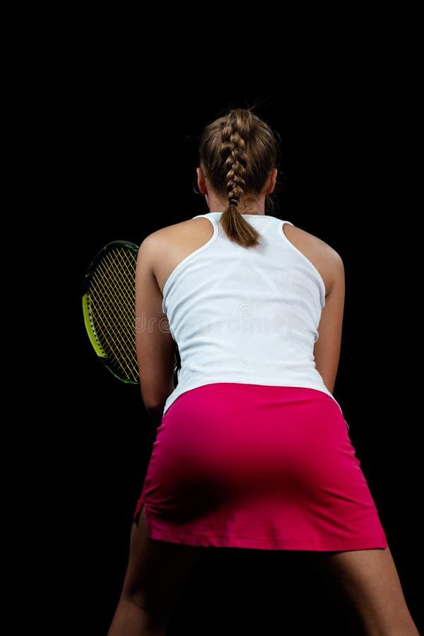 De mooie speler van het meisjestennis met een racket op donkere achtergrond met lichten royalty-vrije stock afbeelding