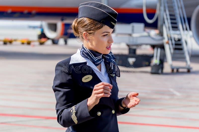 De mooie stewardess kleedde zich in officiële donkerblauwe eenvormig van de Luchtvaartlijnen van Aeroflot op vliegveld Passagiers royalty-vrije stock foto