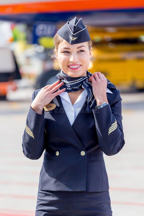 De mooie stewardess kleedde zich in officiële donkerblauwe eenvormig van de Luchtvaartlijnen van Aeroflot op vliegveld Passagiers stock foto