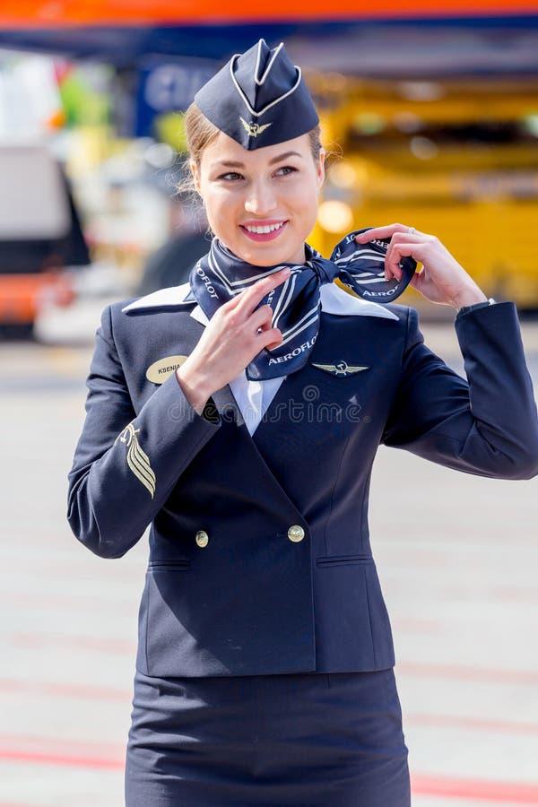 De mooie stewardess kleedde zich in officiële donkerblauwe eenvormig van de Luchtvaartlijnen van Aeroflot op vliegveld Passagiers stock afbeelding
