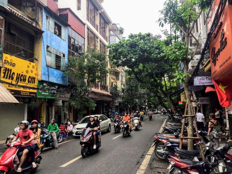 De mooie straten zijn bezig in Hanoi met plaatselijke bewoners die drijven te werken en rond de stad stock afbeelding