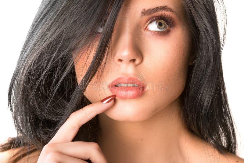 De mooie thinkful dichte omhooggaande studio van het donkerbruine vrouwengezicht op wit stock fotografie
