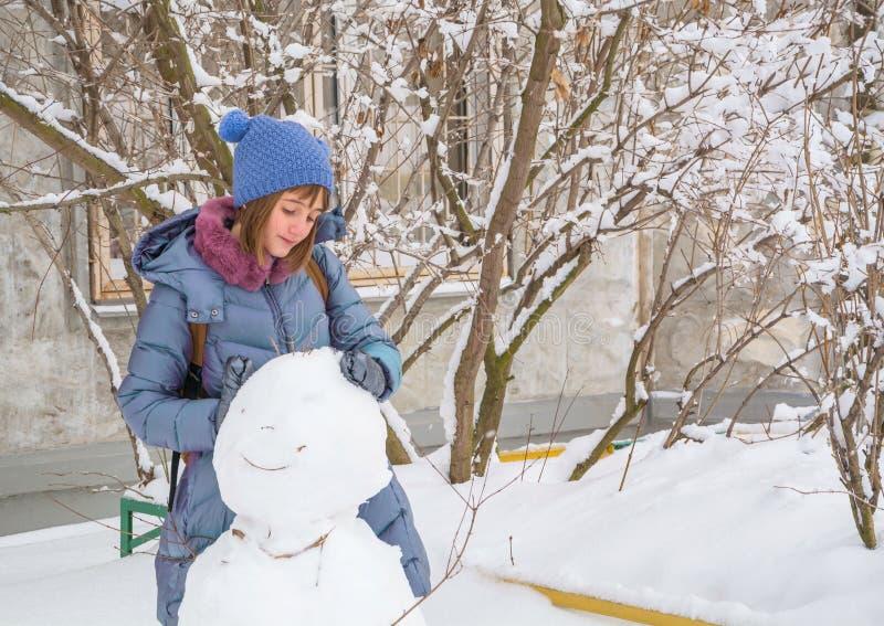 De mooie tiener beeldhouwt een sneeuwman royalty-vrije stock foto
