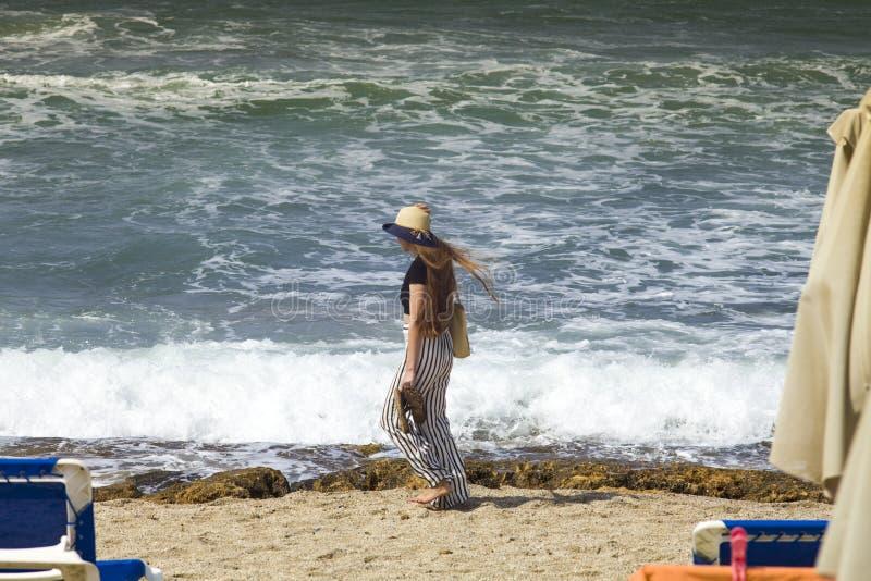 De mooie tiener gaat op het strand Het meisje met haar lang haar loopt op het strand in Griekenland royalty-vrije stock foto's