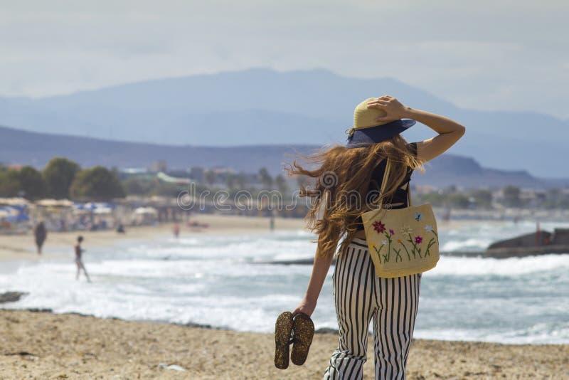 De mooie tiener gaat op het strand Het meisje met haar lang haar loopt op het strand in Griekenland stock fotografie