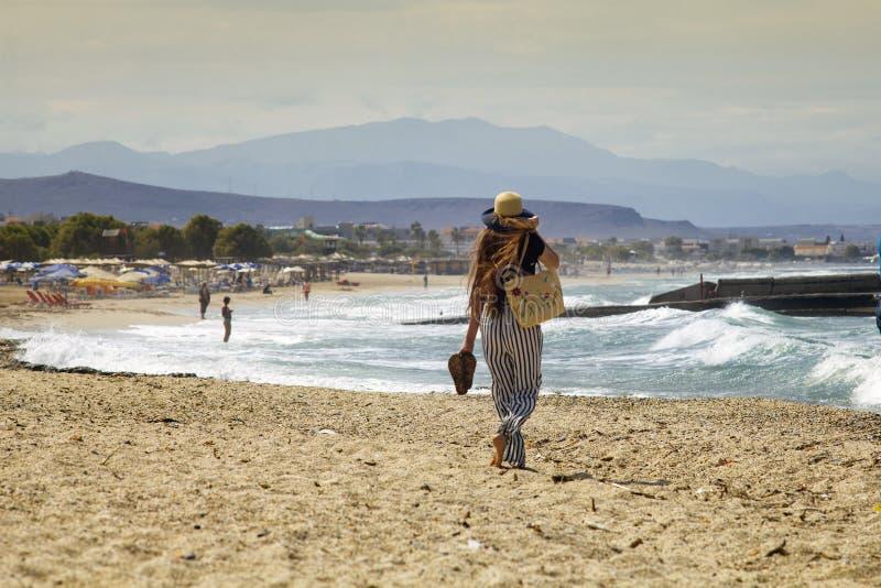 De mooie tiener gaat op het strand Het meisje met haar lang haar loopt op het strand in Griekenland stock foto's