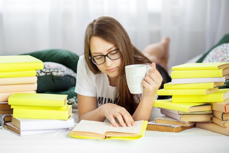 De mooie tiener leest een boek en drinkt thee in de ruimte Concept onderwijs, hobby, studie en de dag van het wereldboek royalty-vrije stock foto
