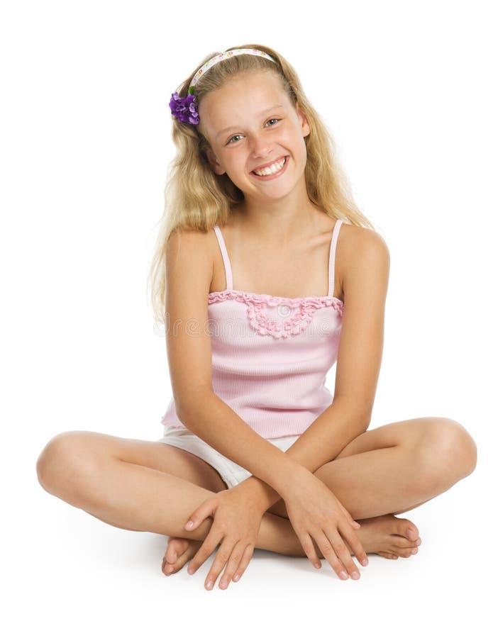 De mooie tiener zit op vloer stock foto