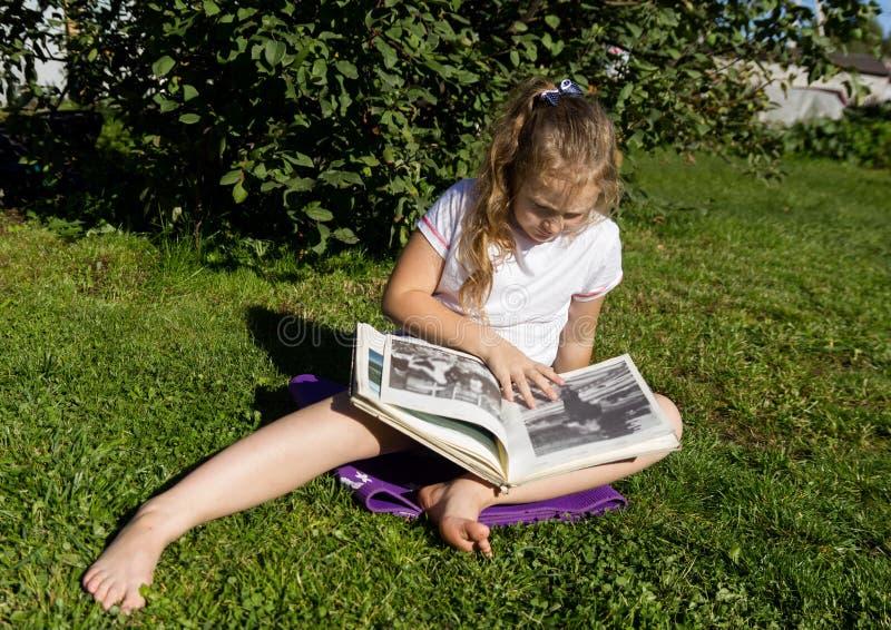 De mooie tienerzitting op een gras in de zomerpark en leest boek stock afbeeldingen
