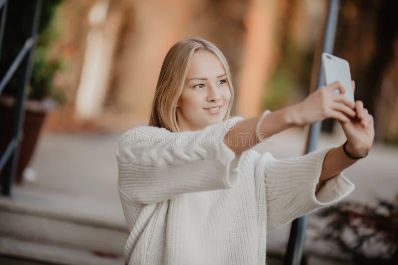 De mooie toevallige vrouw van de blonde modieuze manier met een telefoon in haar hand maakt selfie Europese gebouwen en straat op stock afbeeldingen