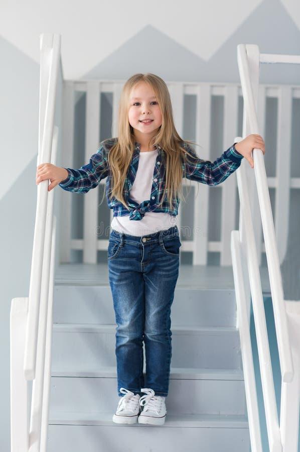 De mooie tribunes van weinig blondemeisje op treden thuis royalty-vrije stock fotografie