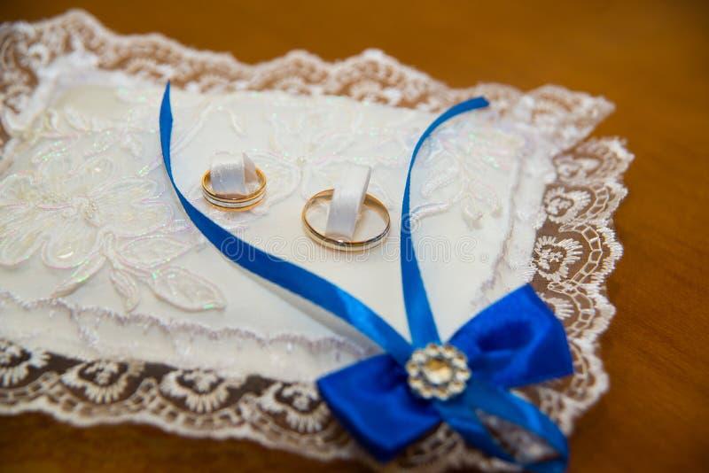 De mooie trouwringen liggen op een hoofdkussen met wit kant en blauwe vlecht royalty-vrije stock afbeeldingen