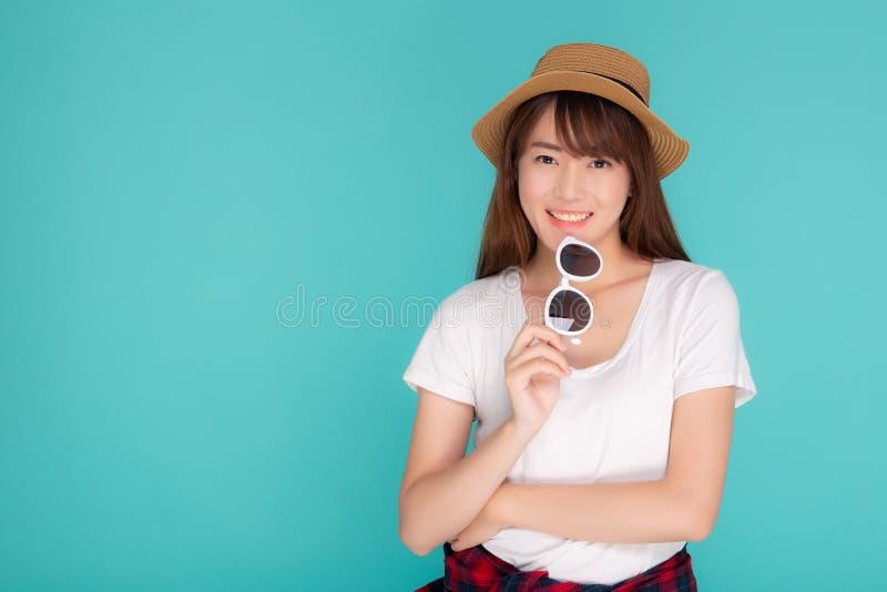 De mooie van de de slijtagehoed en holding van de portret jonge Aziatische vrouw zonnebril die zekere uitdrukking glimlachen geni stock afbeelding