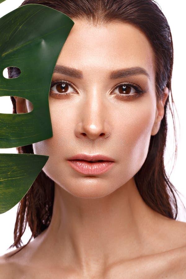 De mooie verse vrouw met perfecte natuurlijke huid, maakt omhooggaande en groene bladeren Het Gezicht van de schoonheid royalty-vrije stock foto