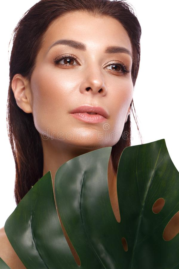 De mooie verse vrouw met perfecte natuurlijke huid, maakt omhooggaande en groene bladeren Het Gezicht van de schoonheid royalty-vrije stock foto's