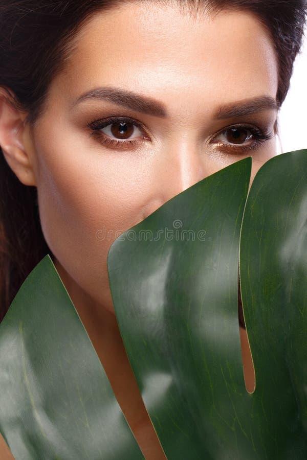 De mooie verse vrouw met perfecte natuurlijke huid, maakt omhooggaande en groene bladeren Het Gezicht van de schoonheid stock foto