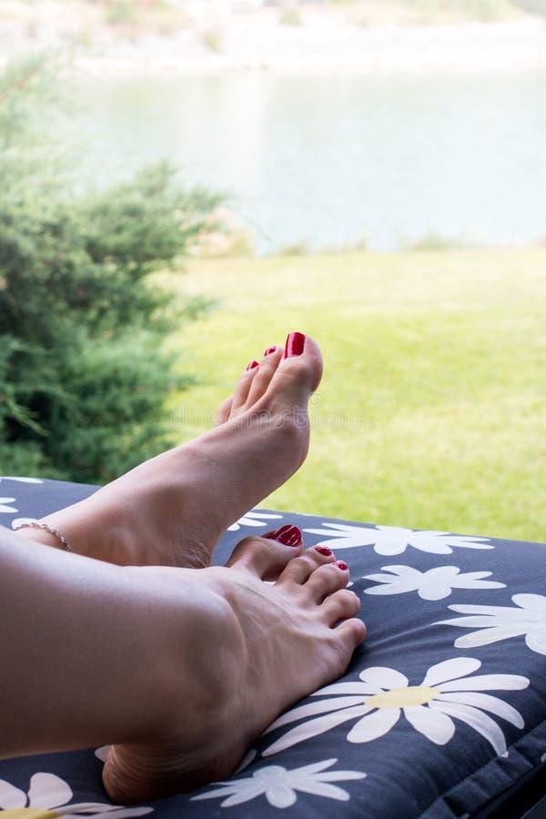 De mooie voeten van vrouw sluiten omhoog met rode spijkerspedicure op tenen die op ligstoel buiten ontspannen stock afbeelding