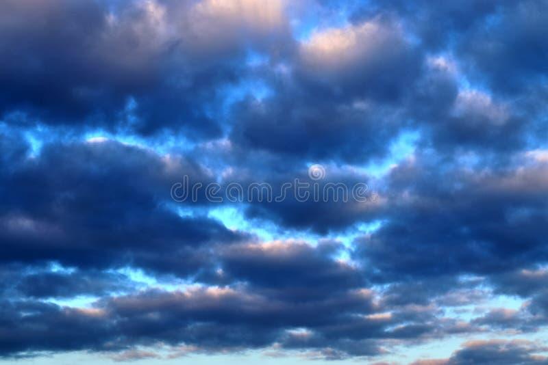 De mooie vormingen van de zonsondergangwolk op een oranje en blauwe hemel royalty-vrije stock foto's