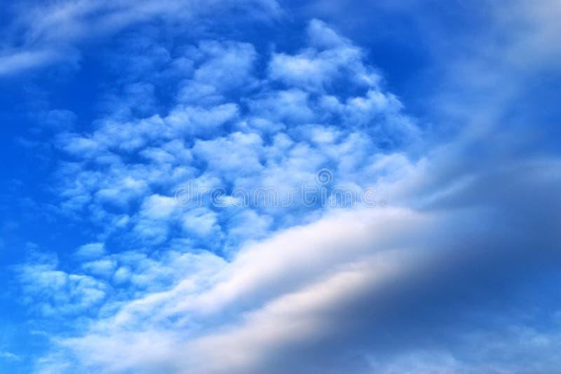 De mooie vormingen van de zonsondergangwolk op een oranje en blauwe hemel stock foto