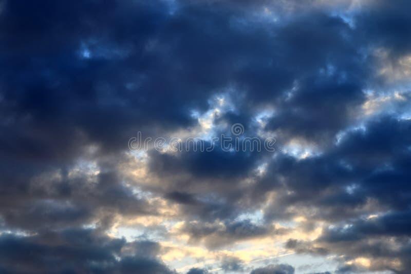 De mooie vormingen van de zonsondergangwolk op een oranje en blauwe hemel stock foto's
