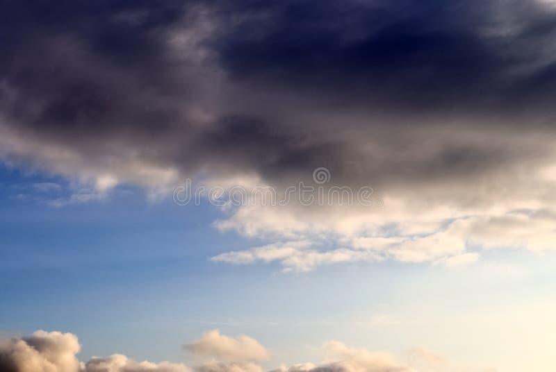 De mooie vormingen van de zonsondergangwolk op een oranje en blauwe hemel royalty-vrije stock foto