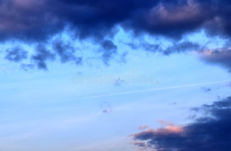 De mooie vormingen van de zonsondergangwolk op een oranje en blauwe hemel stock afbeelding