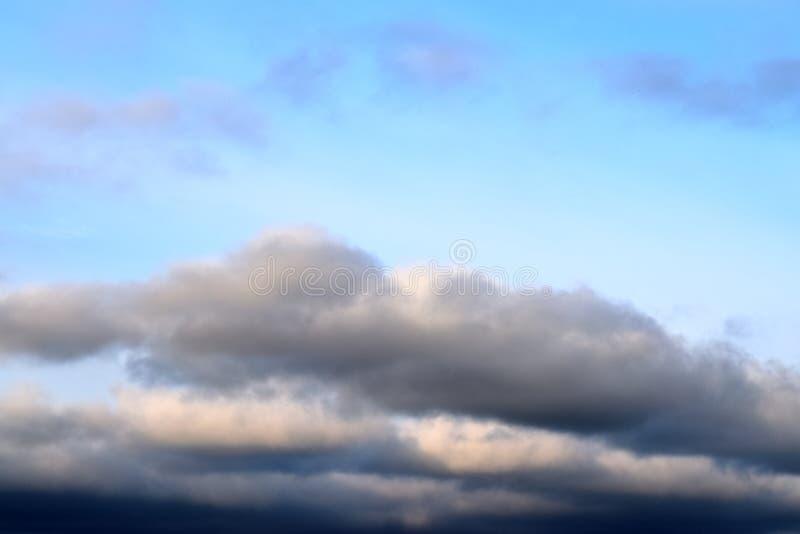 De mooie vormingen van de zonsondergangwolk op een oranje en blauwe hemel stock fotografie