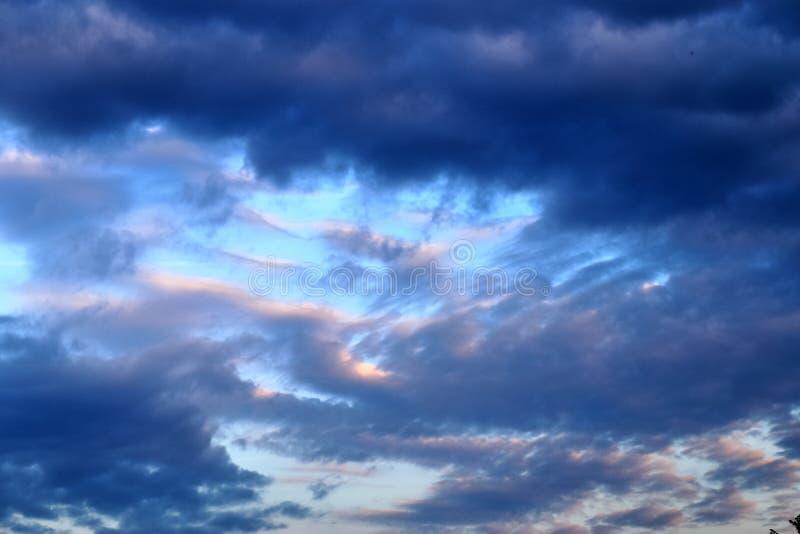 De mooie vormingen van de zonsondergangwolk op een oranje en blauwe hemel royalty-vrije stock afbeelding