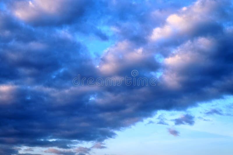 De mooie vormingen van de zonsondergangwolk op een oranje en blauwe hemel royalty-vrije stock fotografie
