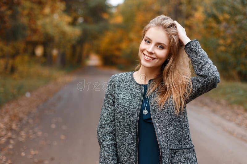 De mooie vrij jonge vrouw in een elegante grijze laag in een groene uitstekende blouse geniet de herfst van weer in een park stock afbeelding