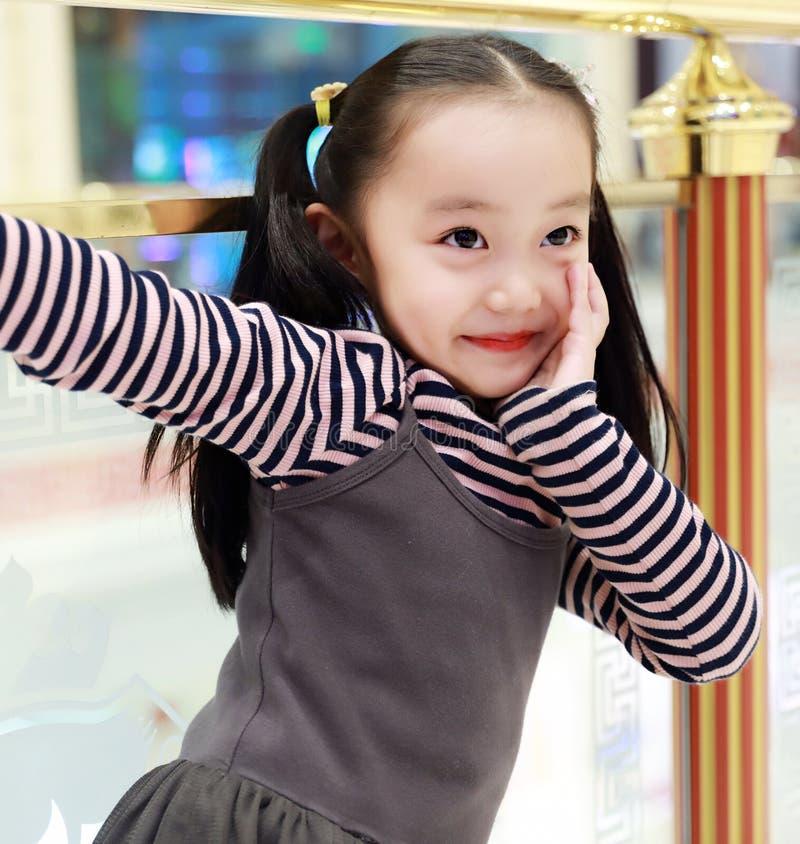 De mooie vrolijke grond van het meisje speelgenoegen op speelplaats stock afbeelding