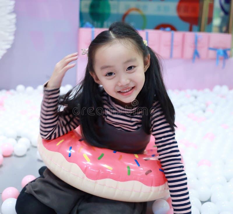De mooie vrolijke grond van het meisje speelgenoegen op speelplaats stock foto